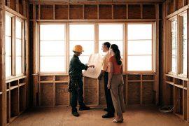 Couple qui regarde les plans de l'extension bois de leur maison avec l'architecte