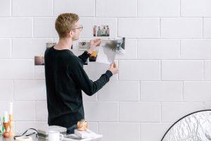 Homme posant des photos sur un mur